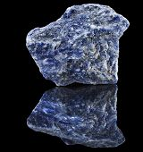 Sodalite stone close up with reflection on black surface background