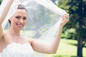 Portrait of happy young bride unveiling self in garden