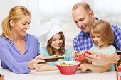 food, family, children, hapiness and people concept - happy family with two kids making dinner at ho
