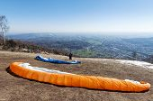 stock photo of lifting-off  - Paraglider pilot preparing for lift - JPG