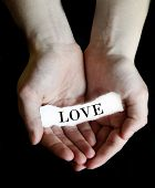 Person hands holding cupping paper message for Love
