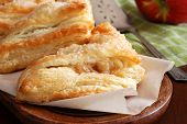 Freshly baked apple turnovers on wooden tray with antique pie server and apple in background.  Rustic still life with natural directional lighting and shallow dof.