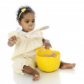 An adorable baby girl looking at a wooden spoon taken from a mixing bowl of pudding.  She's wearing