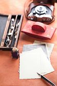 retro photos , vintage ink , pen, blotter and camera on old leather table