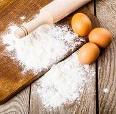 flour, eggs, cinnamon on wooden background