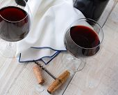 Two wineglasses of red wine on a wood table with antique cork screw. Horizontal format shot from a h