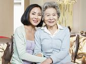 pic of mother law  - asian mother and adult daughter sitting on couch smiling - JPG
