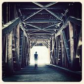 Woman walking towards the sunlight from a covered bridge. Filtered to look like an aged instant phot