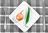 Green Chili Pepper And Onion On A White Plate