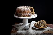 stock photo of sponge-cake  - Marble bundt cake on wooden table black background - JPG