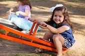 picture of seesaw  - Sweet little girl and her friends having fun in a seesaw in a park and smiling - JPG