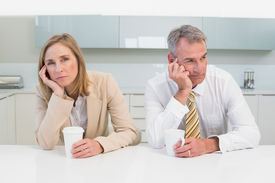 picture of not talking  - Unhappy business couple not talking after an argument in the kitchen at home - JPG