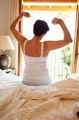 Rear View Of Woman Waking Up In Bed In Morning