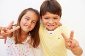 Hispanic Boy And Girl Standing By Wall Making Peace Sign