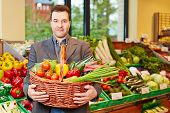 Smiling man carrying basket full of fresh vegetables in a supermarket