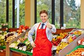 Smiling store manager in a supermarket holding his thumbs up