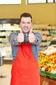 Happy salesman holding both his thumbs up in a supermarket