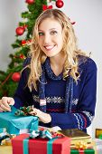 Smiling woman wrapping many presents for christmas