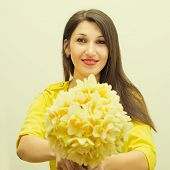 beautiful young happy woman gives bouquet of flowers