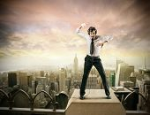 Young businessman dancing on the top of a building