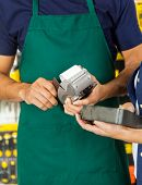 Midsection of worker swiping credit card with woman holding tool set in hardware store