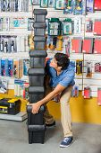 Full length of young man carrying stacked heavy toolboxes in hardware shop