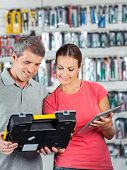 Man and woman with digital tablet analyzing toolkit in hardware store