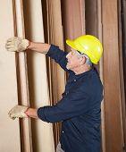 Side view of senior carpenter arranging wooden planks in workshop
