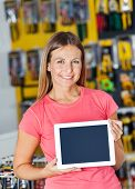 Portrait of smiling mid adult woman showing digital tablet in hardware store