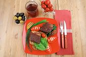 roast meat : beef (pork) steak garnished with vegetables , juice and olives on red plate over wooden