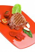 meat food : roast beef garnished with green lettuce and red chili hot pepper on red plate isolated o