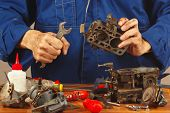 Repairman repairing parts of old automobile engine in workshop