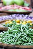 Local street market colorful vertical background with shallow depth of field. Green beans pods and other vegetables