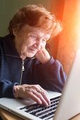 Old woman checks the mail on a laptop.