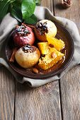 Baked apples on plate on table close up