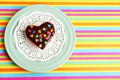 Delicious rainbow mini cake on paper napkin, on bright background