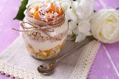 Healthy breakfast - yogurt with  fresh peach and muesli served in glass jar, on color wooden backgro