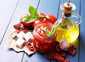 Sun dried tomatoes in glass jar, olive oil in glass bottle and feta cheese on color wooden background