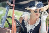 Attractive Young Woman in Twenties Outfit Checking Makeup in Antique Automobile.