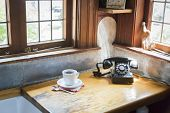 Classic Antique Phone and Cup of Coffee in Old Kitchen Setting.