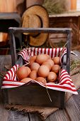Eggs in wooden basket on table close-up