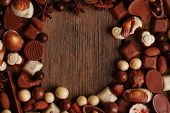 Frame of different kinds of chocolates on wooden table close-up