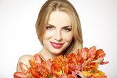 Beautiful and attractive sexy smiling blonde young adult girl with the bouquet of red and yellow tul