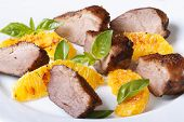 stock photo of roast duck  - slices of roasted duck meat fillet with orange and basil close - JPG