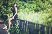 Girl in black dress on fence