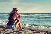 young woman with sunglasses and jeans shorts  sit on sandy beach by the sea enjoy in sunset