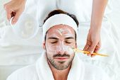 stock photo of beauty parlour  - Portrait of man with clay facial mask in beauty spa - JPG