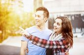 Romantic interracial young couple standing together pointing outside in sunset light with intentiona
