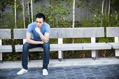 Concerned young asian man sitting on park bench with copy space