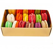 Assortment of multicolored macaroon different lie in the cardboard box with the top view